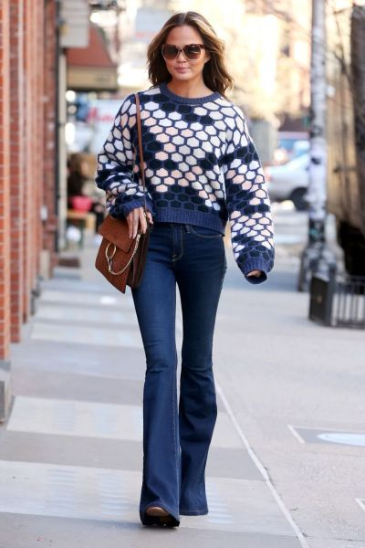 Fashion model Chrissy Teigen, wearing bell bottom jeans and honeycomb sweater, carries shopping bags of food and a box from Fresh Direct on April 1, 2015 in New York City Pictured: Chrissy Teigen Ref: SPL989891 010415 Picture by: Christopher Peterson/Splash News Splash News and Pictures Los Angeles:310-821-2666 New York:212-619-2666 London:870-934-2666 photodesk@splashnews.com